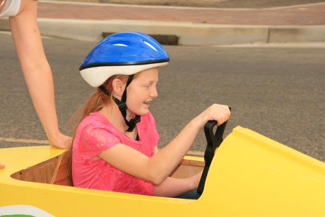 2016 Kiwanis Soap Box Derby girl in helmet driving yellow car